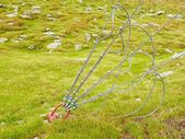 Sling and scrap in green yard, iron twisted rope fixed by screws snap hooks and grommets at anchor in ground. — Foto Stock