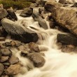 Danger floody stream in quick run over rocks. Blurred waves of Alpine river running over boulders and stones, bubbles in the water . — Stock Photo #52141593