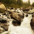 Danger floody stream in quick run over rocks. Blurred waves of Alpine river running over boulders and stones, bubbles in the water . — Stock Photo #52141603
