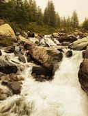 Danger floody stream in quick run over rocks. Blurred waves of Alpine river running over boulders and stones, bubbles in the water . — Stock Photo