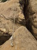 Twisted iron rope fixed in sandstone rock by screws snap hooks. Detail of rope end anchored into block — Stock Photo