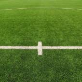 Closeup view to white lines on artificial grass field on football playground. Detail of a cross of lines in a soccer field. Plastic grass and finely ground black rubber. — Stock fotografie