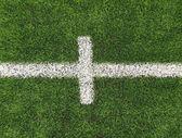крупным планом вид белые линии на искусственной травой поле на футбольное поле. деталь креста линий в футбольное поле. пластиковая трава и мелко местах черный каучук. — Стоковое фото