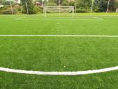 Detail of a penalty point in fron of goalkeeper field. Football playground view of artificial grass field, gate at the end. Plastic grass and finely ground black rubber. — Stock Photo