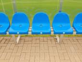 New blue plastic seats on outdoor stadium players bench, chairs with new paint below transparent plastic roof. Plastic football green turf playground. — Stock fotografie