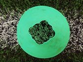 Bright green blue plastic cone on painted white line. Plastic football green turf playground with grind black rubber in core. — Stock fotografie