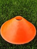 Artificial green plastic grass in background with  bright orange plastic cone. Mark on winter footbal playground. — Stock Photo