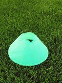Plastic football green turf playground with crushed black rubber in core and bright green blue plastic cone. — Stock Photo