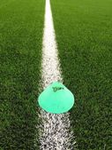 Bright green blue plastic cone on painted white line. Plastic football green turf playground with grind black rubber in core. — Stock Photo