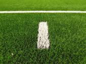 Closeup view to white lines on artificial grass field on football playground. Detail of a cross of lines in a soccer field. Plastic grass and finely ground black rubber — Zdjęcie stockowe
