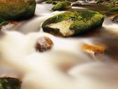 Big mossy boulders in foamy water of mountain river. Light blurred water with reflections. — Stock Photo