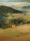 Suny sunrise in a beautiful countryside of Czech-Saxony Switzerland park. Gentle fog above village church. Warm sun rays fight with cold ground mist in valley. — Stock Photo