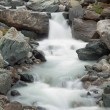 Steep stony stream bed of Alpine brook. Blurred waves of stream running over boulders and stones, high water level after heavy rains. — Stock Photo #52629473