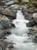 Steep stony stream bed of Alpine brook. Blurred waves of stream running over boulders and stones,  high water level after heavy rains. — Stock Photo