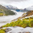 First snow on Alpine meadow.  Quick stream is falling down over slipper  stones  to deep misty valley.  Snowy peaks of Alps mountains in background. — Stock Photo #52805041