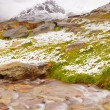 First snow on Alpine meadow.  Quick stream is falling down over slipper  stones  to deep misty valley.  Snowy peaks of Alps mountains in background. — Stock Photo #52805077