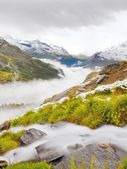 First snow on Alpine meadow.  Quick stream is falling down over slipper  stones  to deep misty valley.  Snowy peaks of Alps mountains in background. — Stock Photo