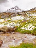 First snow on Alpine meadow.  Quick stream is falling down over slipper  stones  to deep misty valley.  Snowy peaks of Alps mountains in background. — Stockfoto