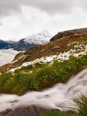 First snow in Alps touristic region. Fresh green meadow with rapids stream. Peaks of Alps mountains in background. Foamy water is running down over slipper stones in snowy green meadow. — Foto de Stock