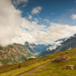 Sharp snowy peaks of Alps mountains above valley full of heavy fog — Stock Photo #53192777