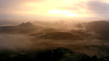 Amazing sunrise in a beautiful mountain of Czech-Saxony Switzerland park. Rocky hills peaks increased from foggy background, the fog is orange due to sun rays. — Stock Video