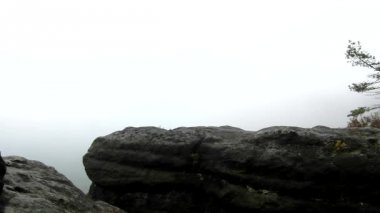 Photographer with tripod standing on rocky view point and taking photos of misty morning landscape. National park Saxon Switzerland in Germany. Melancholic autumn morning. — Stock Video