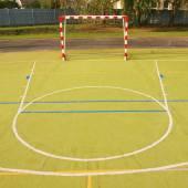 Parque infantil de handebol exterior vazio, superfície plástica de luz verde no chão e linhas limites azul branco. — Foto Stock