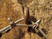 Detail of rope end anchored into sandstone rock. Iron twisted rope fixed in block by screws snap hooks. — 图库照片