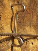 Detail of rope end anchored into sandstone rock. Iron twisted rope fixed in block by screws snap hooks. — Foto Stock