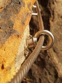 Detail of rope end anchored into sandstone rock. Iron twisted rope fixed in block by screws snap hooks. — Stockfoto