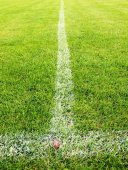 Cross of painted white lines on plastic football grass. Artificial green turf texture. — Stock Photo