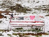 Abandoned red snowy bench with  poles and freeze clothes. Misty morning on the hill in Switzerland Alps. Red wooden bench on meadow, cold snowy and misty weather. — Stock Photo