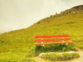Abandoned red bench on hill view point. September misty evening on the hill in Switzerland Alps. Red wooden bench on meadow, cold rainy and misty weather. — Stock Photo