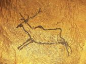 Black carbon paint of deer on sandstone wall, copy of prehistoric picture. Abstract children art in sandstone cave. — Stock Photo