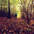 Man walking in colorful forest in autumn mist — Stock Photo #56852351