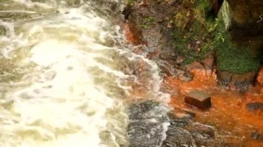 Fast full-flowing foamy water between sandstone rocks, orange sediments on dirty bank. Deep riverbed hewed into sandstone block — Stock Video