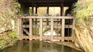 Water of small river flow at historical wooden weir. Terrible smell water with bubbles and reflection. Stony walls of weir — Video Stock