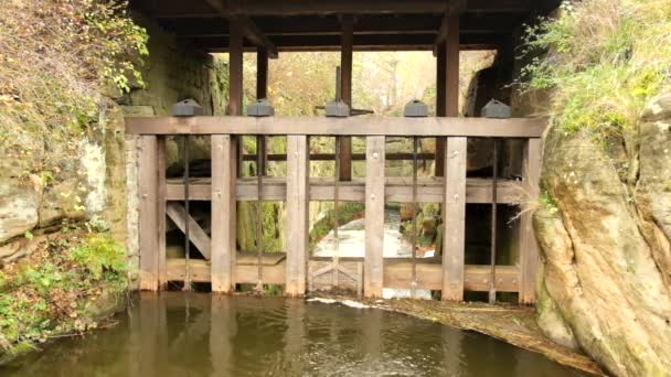 Water of small river flow at historical wooden weir. Terrible smell water with bubbles and reflection. Stony walls of weir — Vidéo