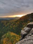 Autumn sunset view over sandstone rocks to fall colorful  valley of Bohemian Switzerland. Sandstone peaks and hills increased from colorful background. — Stock Photo