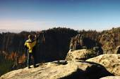 Man is taking photos on peak in rock empires park and watching over autumn misty valley. Sunny fall day. — Stock Photo