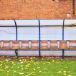 Old plastic seats on outdoor stadium players bench, chairs with worn paint below yellow roof.  Autumn leaves, end of football season. — Stock Photo #59823317
