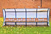 Old plastic seats on outdoor stadium players bench, chairs with worn paint below yellow roof.  Autumn leaves, end of football season. — Stock Photo