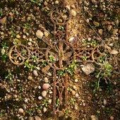 Broken iron rustic crucifix on mossy sand. Abandoned symbol of religion. — Stock Photo