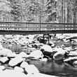 Winter at river and old footbridge. Big stones in stream covered with fresh powder snow and lazy water with low level. Reflections of forest  in water level. — Stock Photo #61263371
