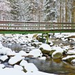 Winter at river and old footbridge. Big stones in stream covered with fresh powder snow and lazy water with low level. Reflections of forest  in water level. — Stock Photo #61263375