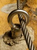 Detail of steel anchor eye and rope end anchored into sandstone rock. Iron twisted rope fixed in block by screws snap hooks. — 图库照片