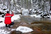 Photograph in red jacket with digital camera in hands is taking photo of winter waterfall — Stock Photo