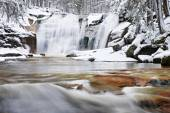 Winter view over snowy boulders to cascade of waterfall. Wavy water level.. Stream in deep freeze. — Stock Photo