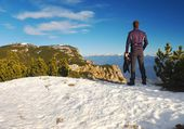 Tourist in black with snowshoes standing on snowy view point. National park Alps park in Italy. Sunny winter morning. — Stock Photo