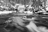 Winter view over snowy boulders to cascade of waterfall. Wavy water level.. Stream in deep freeze. — Foto de Stock